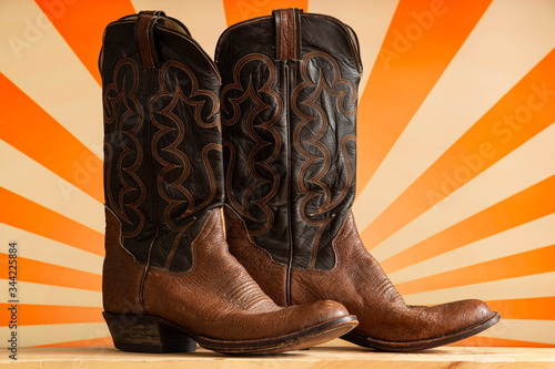 Old country western cowboy boots against a retro pop orange striped background Canvas-taulu