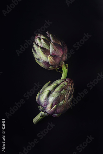 Photo Fresh raw artichokes on black background