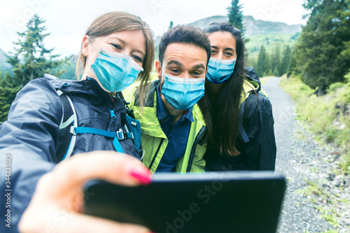 Valokuvatapetti Hiking friends in protective masks standing on mountain terrain taking a selfie