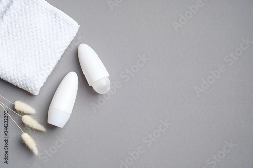 Photo Roll-on deodorant packaging with dry flowers and towel on grey background