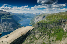 Trolltunga. Troll Language In Norway. Rocky Ledge Above The Fjord. Natural Landmark Of Norway. Girl Sitting On The Edge Of A Rocky Cliff