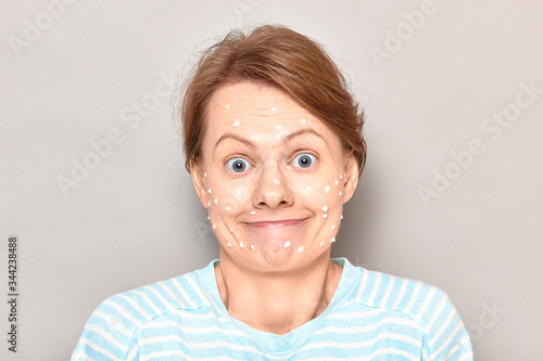 Fotografie, Obraz Portrait of funny goofy cheerful girl with drops of face cream on skin