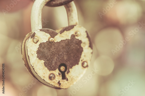 Photo Vintage one large metal padlock with a hole in the form of a heart and with rusty metal from corrosion is closed and secured