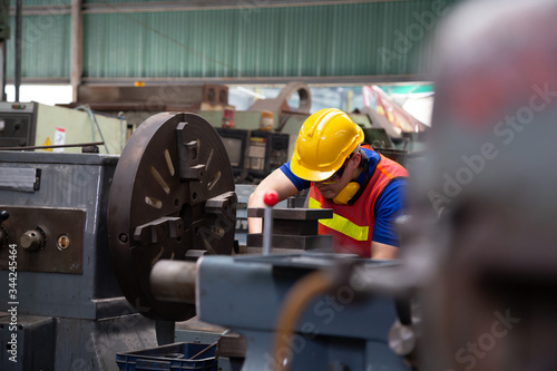 Asian mechanical engineer operating industrial lathe machine and working at indu Wallpaper Mural