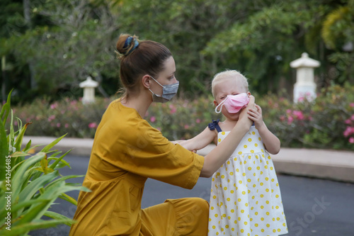 Mummy struggles to put medical mask on her child's face Фотошпалери