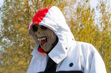 A Man In A Jacket With A Hood On His Head And A Scary Zombie Mask On His Face