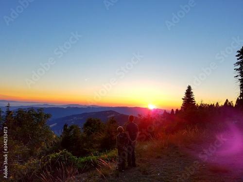 Fototapeta Rear View Of Boys Standing On Field Against Mountain Range During Sunset obraz na płótnie