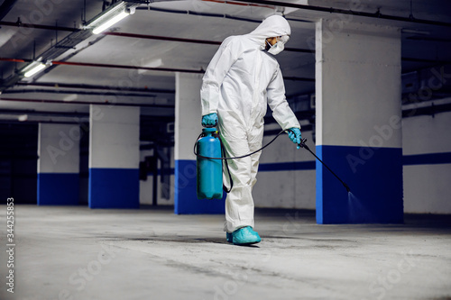 Worker in sterile uniform and mask walking trough underground garage and sterilizing surface Canvas Print