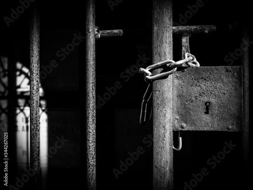 Cerradura y cadena en la reja de una tumba en el cementerio