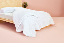 White Comforter On Wooden Bed