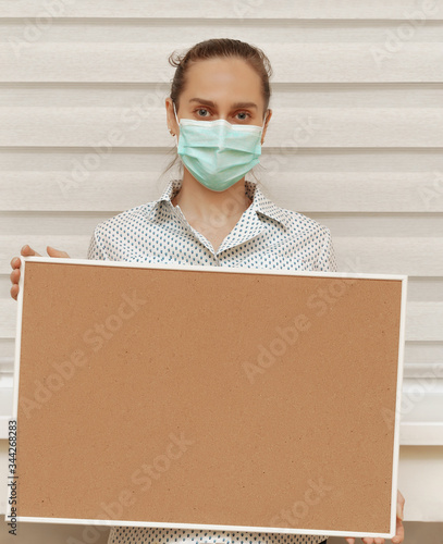 Photo A young woman in a mask holds an empty cork board in her hands, standing on a white background
