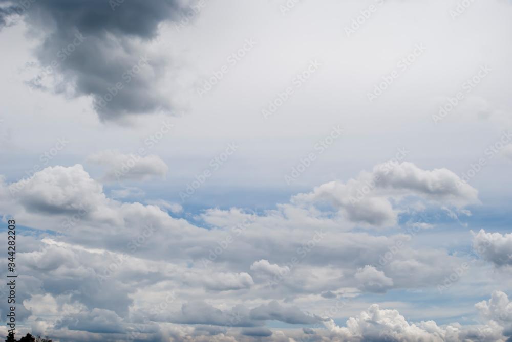 Fototapeta Zdjęcie z miejscem na tekst przedstawiające jasne,  błękitne niebo z chmurami. Jasne i ciemne chmury na tle jasnego nieba.