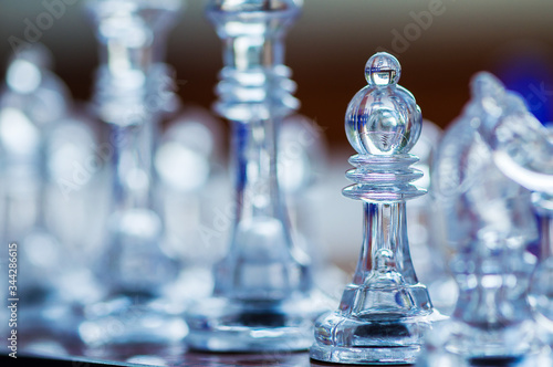 Close-up of a transparent bishop chess piece sitting on a chessboard Canvas Print