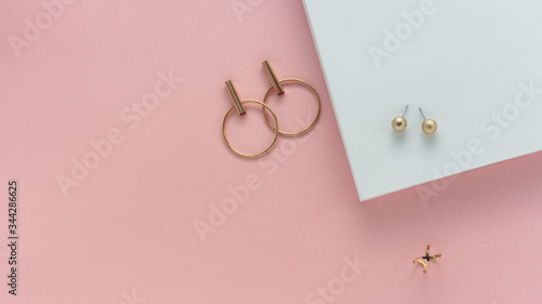 Fototapeta Golden stud earrings and golden ring on white and pink paper background with cop