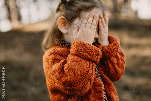 Fényképezés Little girl playing hide and seek, peek a boo, covering face with hands