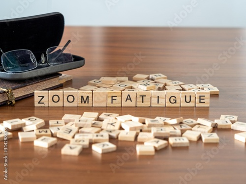 Fototapeta zoom fatigue concept represented by wooden letter tiles on a wooden table with glasses and a book obraz