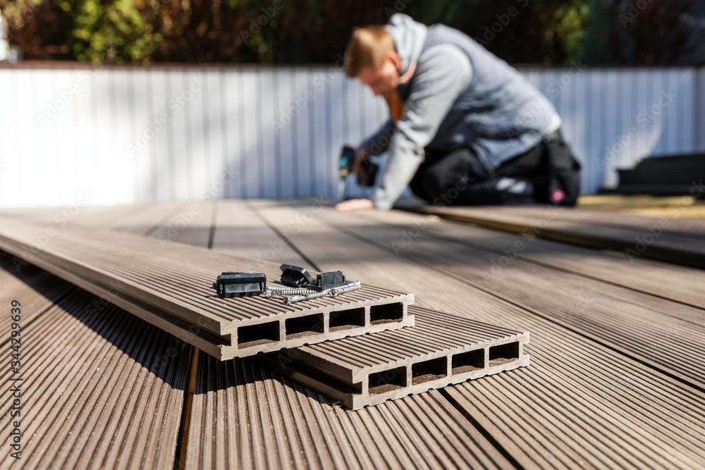 Fototapeta wpc terrace construction - worker installing wood plastic composite decking boards - obraz na płótnie
