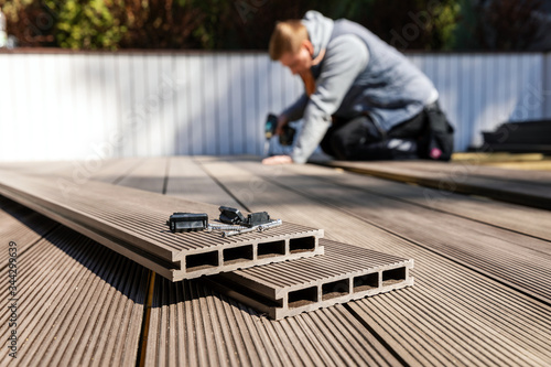 wpc terrace construction - worker installing wood plastic composite decking boar Fototapet