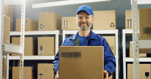 Leinwand Poster Portrait of happy delivery man in uniform and cap smiling cheerfully to camera with carton box