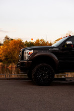 Front-side View Of Pick-up Truck Ford F-250 . A Big Black Car. On The Background Of The Lake.