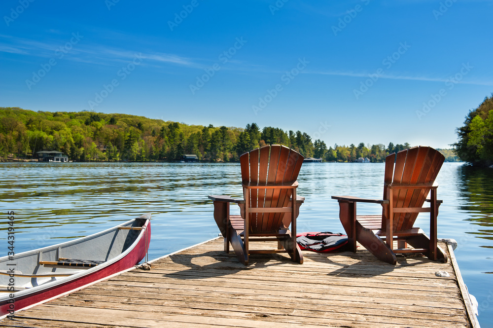 Fototapeta Two Adirondack chairs on a wooden dock on a lake in Muskoka, Ontario Canada. A red canoe is tied to the pier. Across the water cottages nestled between green trees are visible.