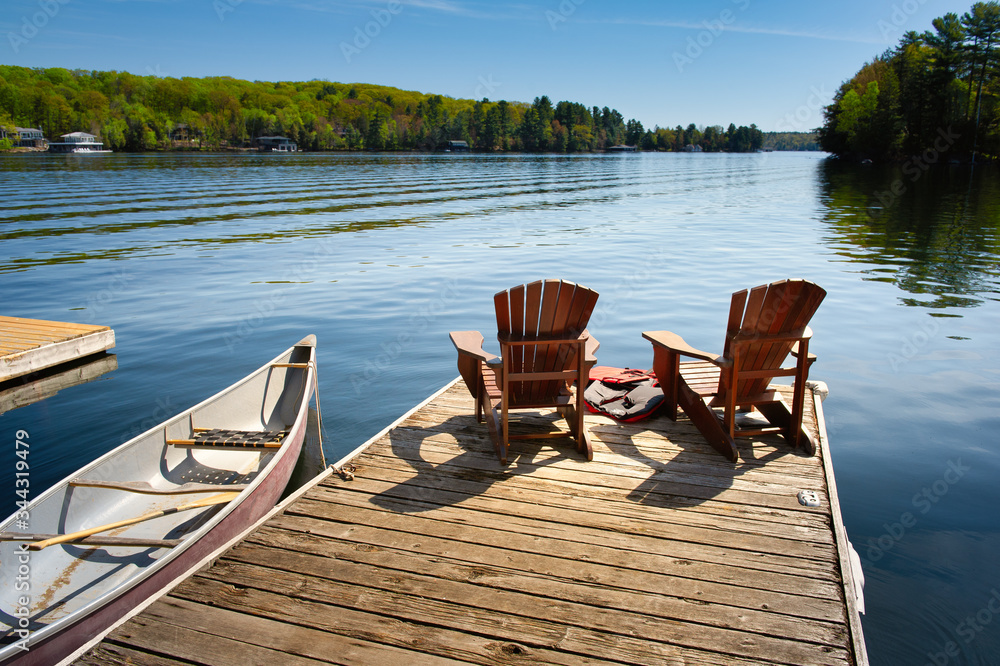 Fototapeta Two Adirondack chairs on a wooden dock facing the blue water of a lake in Muskoka, Ontario Canada. A red canoe is tied to the pier. Across the water cottages nestled between green trees are visible.