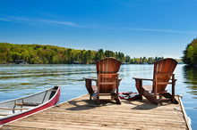Two Adirondack Chairs On A Wooden Dock On A Lake In Muskoka, Ontario Canada. A Red Canoe Is Tied To The Pier. Across The Water Cottages Nestled Between Green Trees Are Visible.