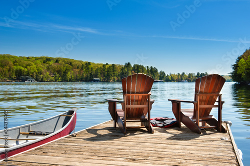 Two Adirondack chairs on a wooden dock on a lake in Muskoka, Ontario Canada Fototapeta