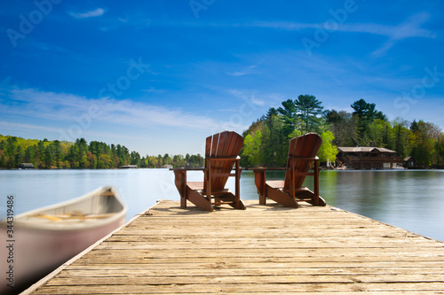 Photo Two Adirondack chairs sit on a wooden dock facing the blue waters of a calm lake