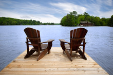 Two Adirondack Chairs On A Wooden Dock Overlooking A Calm Lake. A Brown Cottage Nestled Between Green Trees Is Visible Across The Water.