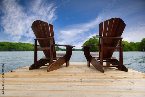 Slika na platnu Two Adirondack chairs on a wooden dock overlooking a calm lake.