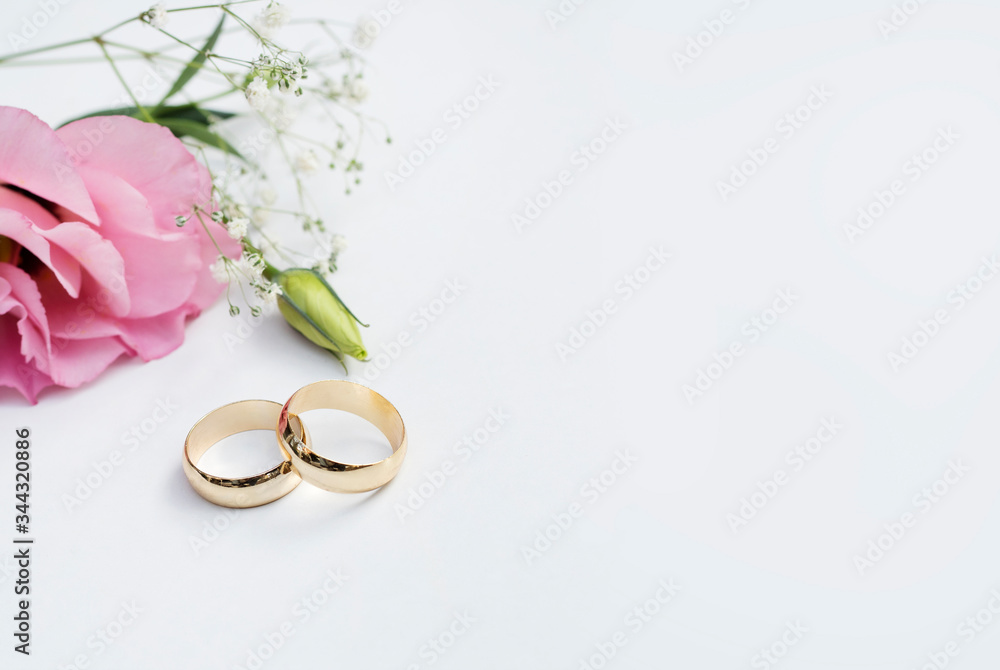 Fototapeta Pink flowers and two golden wedding rings on white background.