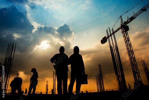 Fotografie, Obraz Silhouette Workers Working At Construction Site Against Cloudy Sky During Sunset