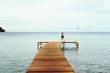 Man Sitting On Pier At Sea Against Sky
