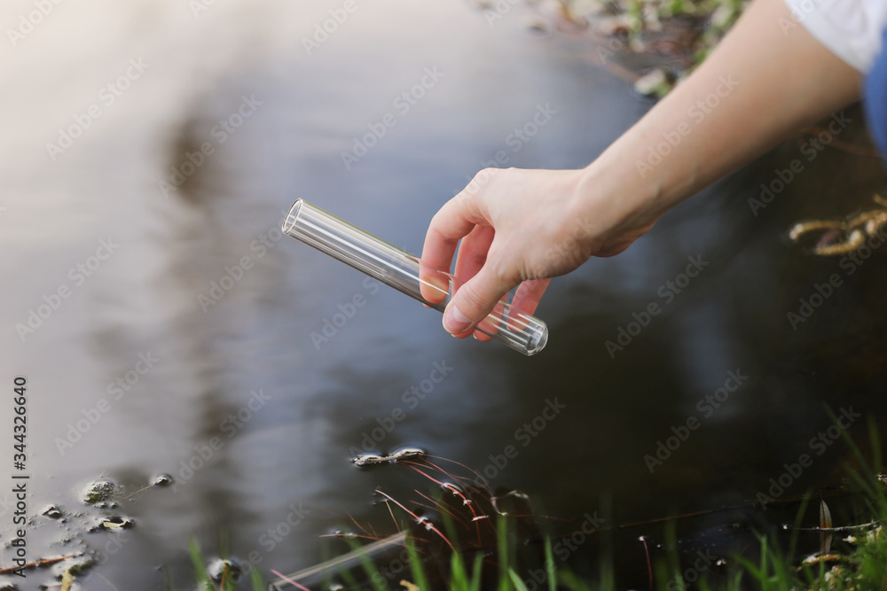 Fototapeta a specialist s hand draws water into a flask from a river for further research in the laboratory. checks the level of water pollution. selective focus