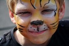 Close-up Portrait Of Boy With Tiger Face Painting