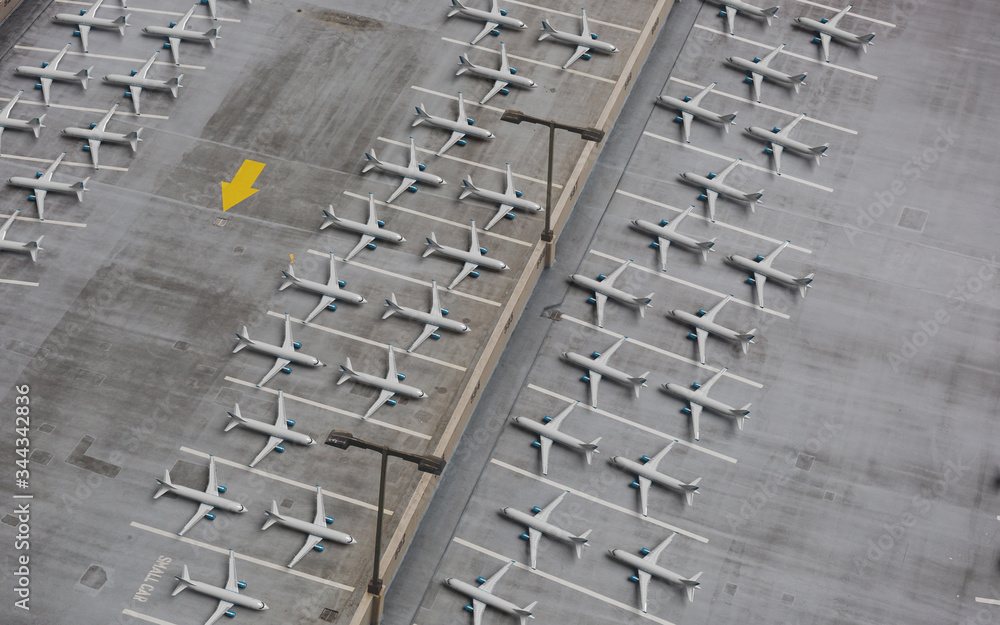 Fototapeta Lockdown of flights concept: Composite image of a parking lot shot from above and 3d rendered airplanes temporarily retired due to very reduced number of flights.