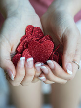Close-up Of Hands Holding Heart Shape Glitters