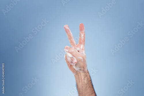 Hand with soap suds making the victory gesture. Fototapeta