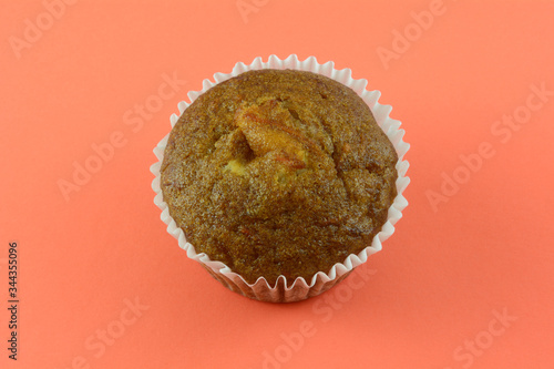Fototapeta Baked carrot muffin in white paper muffin cup in orange background