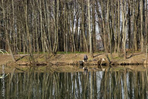 Valokuvatapetti fisherman on the shore of a city lake or river