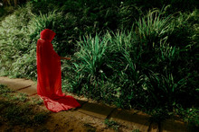 Woman Wearing Red Riding Hood Cape While Standing By Plants