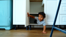 Family At Home Concept, Little Boy Playing Hide And Seek. A Happy Child Looks Out Of The Closet In The Kitchen.