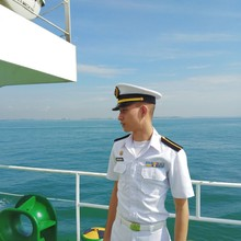 Young Navy Officer Standing On Ship Sailing In Sea Against Sky