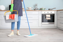 Young Woman Mopping Floor In K...