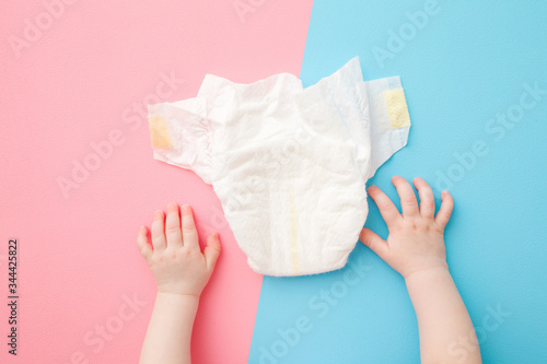 Baby hands and white diaper on light pink blue table background Poster Mural XXL
