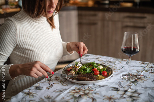 Fotografie, Tablou The dark-haired girl in a beige dress eats a steak at home
