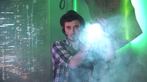 Fotografie, Obraz Medium shot of filmmaker looking at camera while using a Fresnel lamp