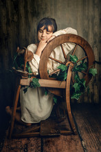 Indoor Portrait Of Young Child Girl With Wool Spinning Wheel On Wooden Background