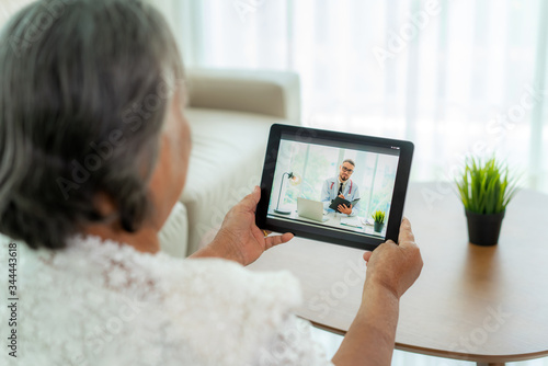 Fotografija Back view of elderly woman making video call with her doctor with her feeling sick on digital tablet online healthcare digital technology service consultation while staying at home